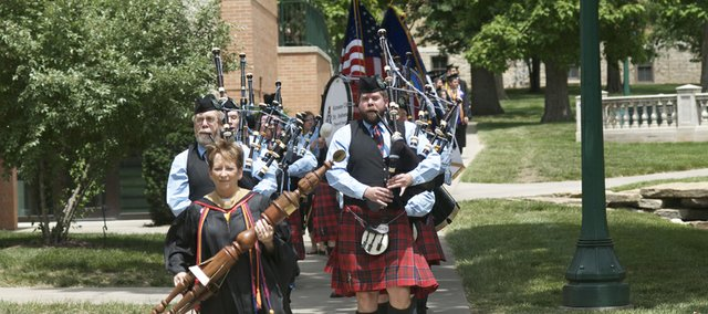 Baker University business professor Martha Harris carries the university's mace Sunday as she leads the Kansas City St. Andrew Pipe and Drum and Baker's undergraduate Class of 2012 on a procession through campus to commencement ceremonies at the Collins Center.