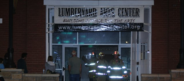 A Baldwin City Fire Department firemen brings a painting out of the Lumberyard Arts Center in downtown Baldwin City after firefighters extinguished a fire in the unfinished rear section of the building.