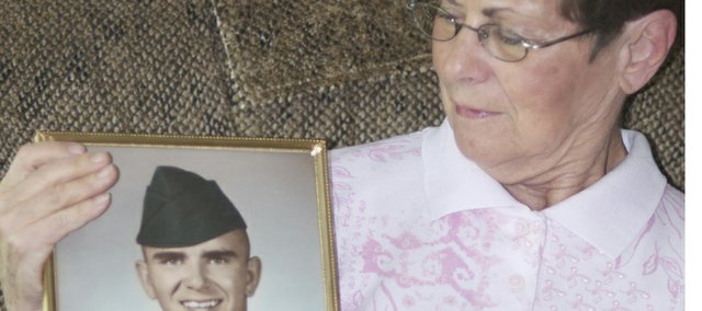 Shirley Rochester looks at a photograph of her younger brother Gary Johnson taken shortly before he was killed in action in the Vietnam War. Rochester remembers her brother as a fun-loving young man who accepted it as his duty to go to a war in which his friends had served.