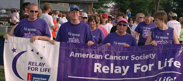 Cancer survivors carry a banner to lead the opening survivor lap at a recent Shawnee-Lenexa Relay For Life. Area Relay For Life events will be raising money for the American Cancer Society this summer.