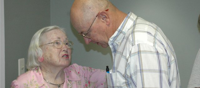 Tom Wyrick, right, leans forward to listen to his former neighbor, Reba Shaw, at her going away party Friday at the Bonner Springs Senior Center. Wyrick lived next to Shaw on Clark Street when he was growing up, and Shaw used to babysit him.