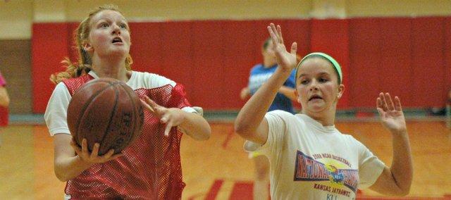 Morgan Galvin, left, drives by Samantha Jones for a layup Thursday at the Tonganoxie High girls basketball camp.
