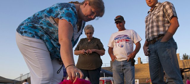 Susan Harrison places a luminary along the track as her mother-in-law Barbara, husband Daryle and son Jake Harrison watch during the Douglas County 2012 Relay for Life event held Friday, June 8, 2012 at the Free State High School track. Barbra said she was there honoring both her daughter and husband.