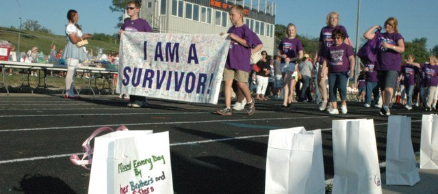 The survivors begin the first lap of the 10th annual Kaw Valley Relay For Life Friday, passing by luminaries like the one on the left, in memory of Marge Berry.