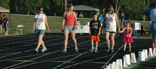 Angie Jones of Bonner Springs walks the track with relatives Mercedies, Andrew, Lori and Samantha Shultz (from left) at Friday's Kaw Valley Relay For Life.
