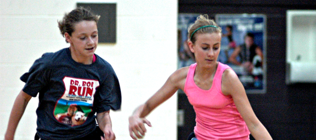Seventh-grader Annabelle Vaught, right, dribbles by eighth-grader Kayleigh Boos Thursday in the McLouth High gymnasium.
