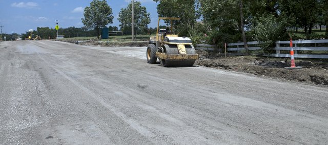 An employee of R.D. Johnson Construction rolls over the freshly applied base for an asphalt overlay Tuesday on the north Sixth Street project. Asphalt was to the first phase of the project from U.S. Highway 56 to Fire Tree Avenue was to be laid Monday and Tuesday but was delayed until Thursday and Friday when soft spots were found in the street's sub-base.