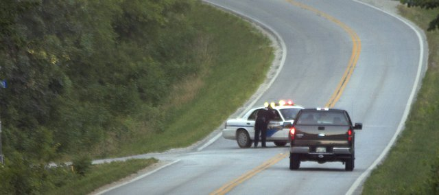 A Baldwin City policeman diverts Friday evening traffic on Douglas County Road 1055 east on North 400 Road at the bottom of Baldwin Hill. A wreck on the hill claimed one life and sent another person to University of Kansas Medical Center.