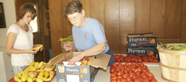 Jennifer Rolland, left, and Joan Toot examine fruit and produce to be given away Monday to children of community families. The summer food distribution open to all in the community is from 6 to 8 p.m. Monday at the Ives Chapel United Methodist Church. 