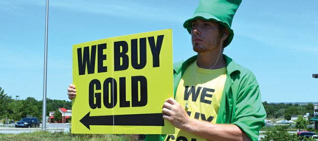 Dressed as a leprechaun, Chris Rachol attracts motorists' attention to the We Buy Gold LLC location at 22342 W. 66th St., Shawnee. It is one of seven We Buy Gold outlets on the Kansas side of the state line that pay cash for gold.