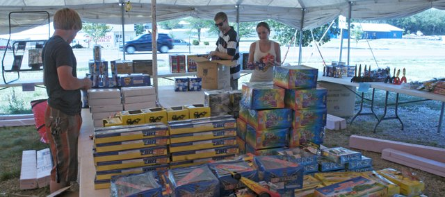 From left, Tyler DeLong, Dan Foye and Aubrey Young stock the Pyro Papa's fireworks stand Friday for the Fourth of July holiday. The stand owned by Young's father is one of four on U.S. Highway 56 offering fireworks in Baldwin City. The city allows fireworks to be sold and discharged from July 1 through July 4 of each year