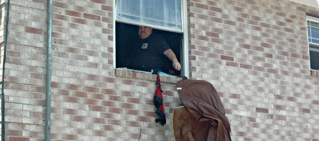 Tonganoxie Fire Chief David Bennett throws burnt debris out the window of an apartment that caught fire Tuesday in Tonganoxie. Nobody was injured in the fire, which occurred at the complex at the intersection of Seventh Street and U.S. Highway 24-40.