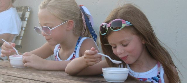 Hadley Skinner (left), 8, and Seville Skinner, 5, of Basehor enjoy some shaved ice at the Basehor Fourth of July celebration at Basehor-Linwood High School.