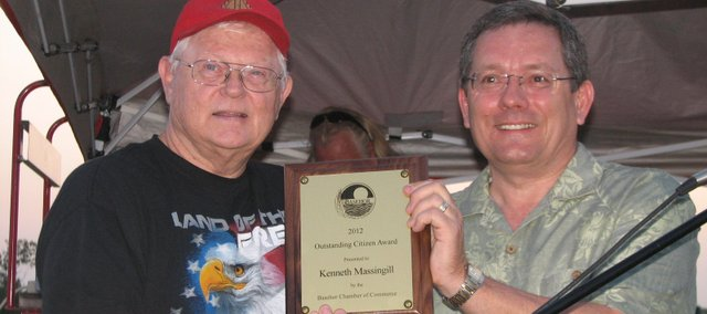 Ken Massingill (left) accepts the 2012 Basehor Chamber of Commerce Outstanding Citizen Award from chamber president Blake Waters during the Basehor July Fourth celebration at Basehor-Linwood High School.