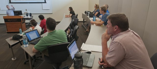 Students listen to Professor John Rury, left, lead a discussion on the subject of American School Reform: Past and Present, last week at the Kansas University Edwards campus in Overland Park.