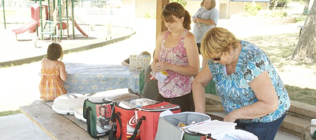 Shelley McKaig, right, prepares with the help of Kim Harris noon lunches for children at a shelter in Grove Park near the swimming pool. McKaig packs the insulated carriers and coolers with food every weekday to bring to the shelter during the summer.