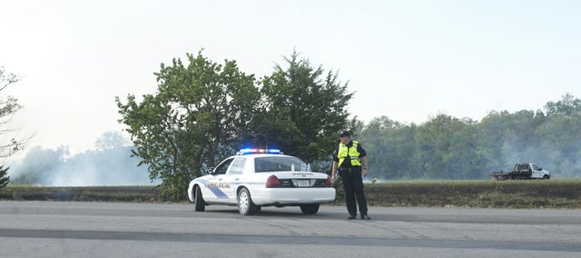 A Baldwin City Police Department office directs traffic on U.S. Highway 56 at Baldwin Elementary School Intermediate Center as fire figthers battle a grass fire north of the highway.