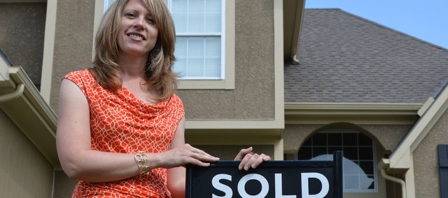 "Beth Kline, who leads the Shawnee-based Kline Group for Reece and Nichols, plants another ""sold"" sign. Kline and another agent have sold 33 homes worth a total of $7.2 million so far this year. For the same period last year, they sold 15 for a total of $2.9 million."