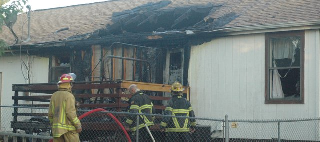 Firefighters tend to a fire Tuesday morning in Tonganoxie. The fire started in the area of the back deck at 505 Laughlin. Owners Dorothy and Walt Deckard were in the home at the time of the fire, but they and Molly, their Yorkie, escaped and were not injured. Firefighters were still trying to determine the cause of the fire Tuesday.