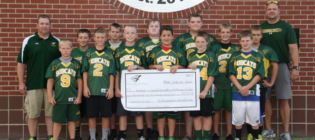 The 2011 Sixth Grade Bobcat Youth Football Team presents a $1,500 check to the Basehor-Linwood Health and Wellness Center. Pictured from left to right are (back row) Rob Cunningham, Logan Schubert, Zach White, Zach Kamm, Ryan Reed, Jacob Coleman, Nolan Ford, BLHS strength and conditioning instructor Ross Schwisow, (front) Jack Wiles, Tuckker Johnson, Zach Howard, Reid Pruitt, Tyler Cunningham and Parker Rusk. Team members not pictured were Dalton Lindelof, Miles Beach, Andrew Sullivan, Lucas Yockel, Luke Willis and Jackson Poe.