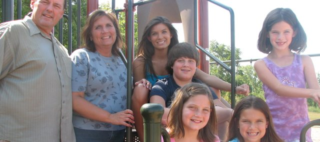 Members of Basehor's McDonnell family can remember their son and brother Jared, who died after an asthma attack in 2009 when he was 9 years old, each time they pass by or play on a neighborhood playground built in his memory. Pictured are Jared's parents, Tim and Jeri, and five of his 15 siblings, clockwise from top left: Meghan, 20, Keith, 13, Caitlyn, 10, Madison, 9, and Paityn, 7. Caitlyn is holding a plaster cast of Jared's hand made by the transplant network that helped with his organ donation.