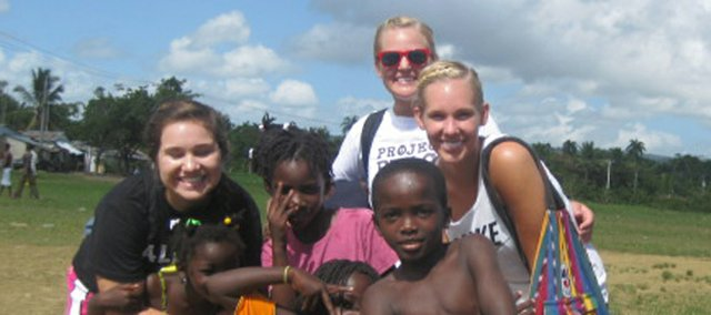 Brooke Morgan, left, and sisters Claire and Alyssa Peterson, top right. pose with some of the children they met on a recent mission trip to the Dominican Republic. The three Baldwin City young women are still working to end human exploitation in that country by selling jewelry that supports the Go Mad Ministry.