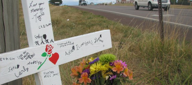 Flowers and a cross with messages from loved ones stand at the site of a Friday two-vehicle accident that claimed the life of Ronda Andrews, a second-grade teacher at Genesis Christian Academy in Tonganoxie. The accident happened at 158th Street and U.S. Highway 24-40 where another Tonganoxie resident, Amanda Bixby, was killed in an accident in February 2007. Friday's accident occurred months before a traffic signal at the intersection is to be finished. Work on the signal is expected to start later this month.