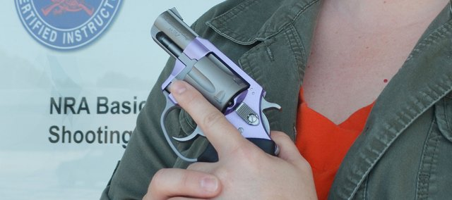Becky Bieker, owner of She's a Pistol, holds her Lavendar Lady, a .38 special. According to Bieker, her new Shawnee business will offer guns and training, with a special emphasis on female customers.