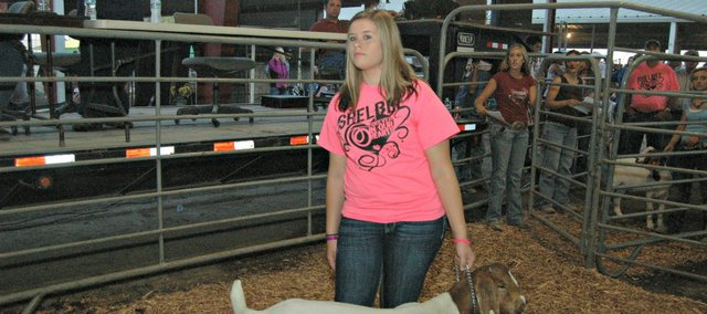 Alyson Heim presents a goat at Friday's 4-H livestock auction. Alyson also displayed her late sister's goat to be auctioned off.