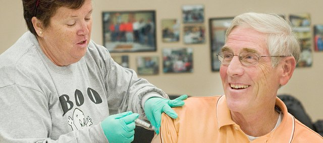 Pat Deaver, with the Douglas County Visiting Nurses, Rehabilitation and Hospice Care Association, gives Jerry Bailey a seasonal flu shot at Tonganoxie High School in this October 2009 file photo.