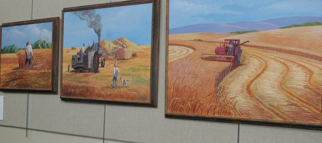 These Felix Summers paintings on display at the Bonner Springs City Library show the history of methods for harvesting wheat.