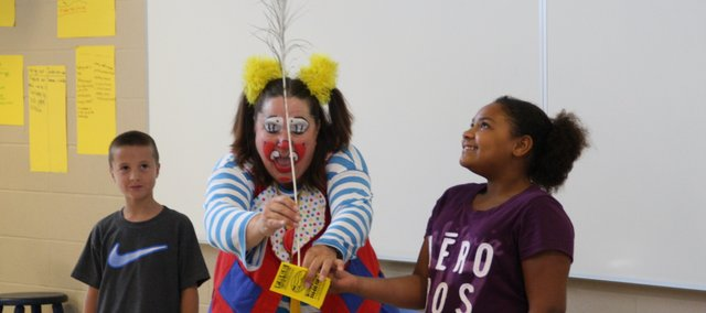 "Skeeter, an ""Advance Clown"" from the Culpepper and Merriweather Circus, performs during an assembly at Basehor Intermediate School on Tuesday with students Luke Oliver and Gabby Benson. Skeeter visited Basehor-Linwood schools in advance of the circus's stop in Basehor next week, which will benefit the Basehor Chamber of Commerce."