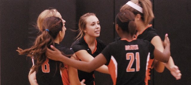 Senior Haley Hoffine celebrates a point with teammates on Tuesday during Bonner Springs' season-opening quad meet against Basehor-Linwood, Baldwin and Eudora. The Braves lost all three matches and will look to grab its first victory Thursday, when it returns to action at home.