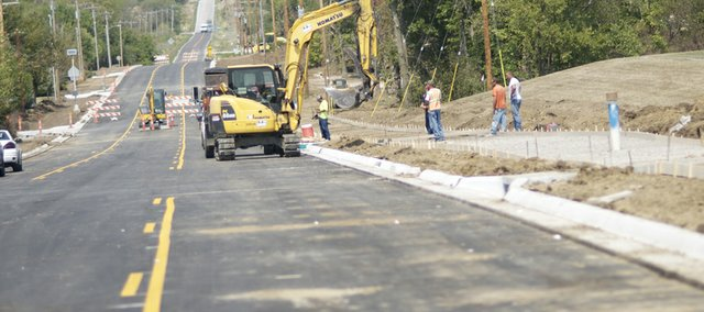 Crews work on the sidewalks along North Sixth Street, which will complete the second phase of the three phase project. The barricades are expected to move north Tuesday with the start of construction on the third and last phase of the project.