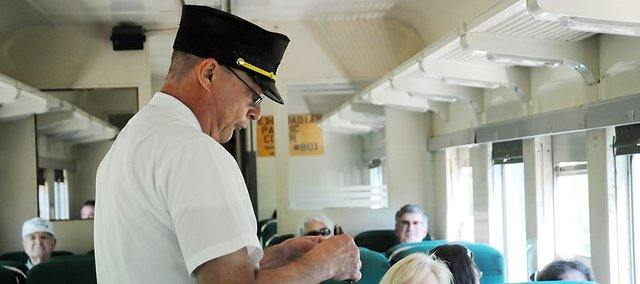 Midland Railway conductor Mark Mosley punches a ticket of one of the passengers attending a recent Railfest. The event returns Labor Day Weekend and features a steam locomotive.
