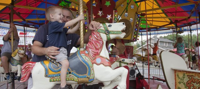 Enjoying a carousel ride together, Scott Komarek and his son Hudson, 2 1/2, took part in Tiblow Days in Bonner Springs. 