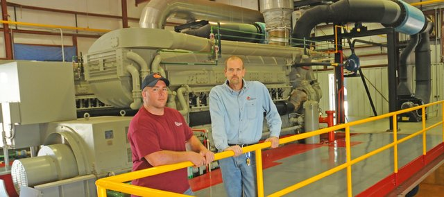 July was a busy month for Baldwin City power plant employees, operator Jarod Franks (left) and plant manager Rob Culley as the city produced 520,436 kilowatt hours of electricity during a month of record heat. Most days, the city purchases power from the open market, a complicated process that has the city making use of experts and a partnership.