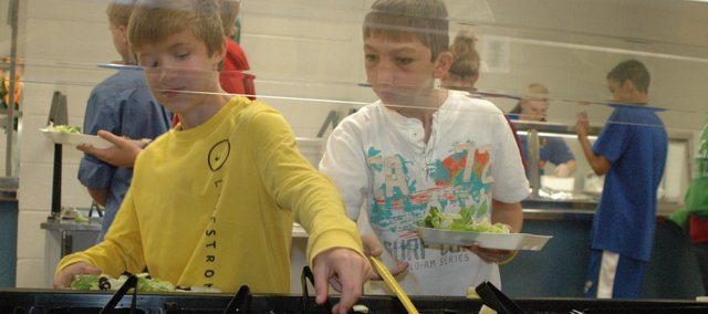 Seventh Graders Coleton Nelson (left) and Jacob Merino load up their trays from the salad bar during lunch Tuesday at Clark Middle School. Students at the school have given the district's new school lunches positive reviews.