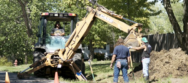 Baldwin city employees Carl Tuttle (left), Johnny Schulmeyer and Steve Gordon, in cab, repair a water line break Tuesday on 10th Street, one of many that have plagued the city during the current drought. Baldwin City's location near the Kansas City metropolitan area affects it and other nearby smaller cities' salary structures.