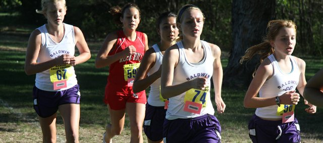 Baldwin runners Faith Peterson, Sienna Durr, Libby Verhaeghe and Addy Dick run as a group with a Rose Hill runner Saturday at the Wamego Invitational. The Baldwin girls cross country team won the event and the boys finished fifth.