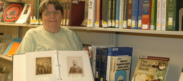 Linda Losier of Bonner Springs holds a photo album including an image of her great-great-grandfather (right) proudly displaying his Congressional Medal of Honor from the Civil War. To find information about her great-great-grandfather and other family members, Losier has used resources like the genealogy books on the shelves next to her at the Kansas Room in the Bonner Springs City Library.