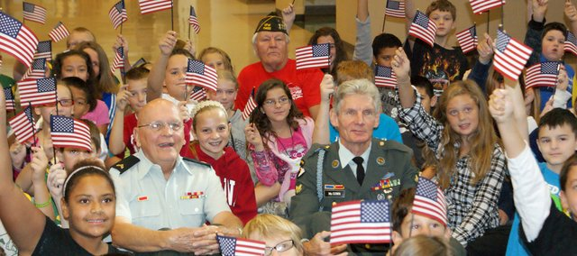 Basehor VFW members Phil Jenkins (left), Steve McGown (right) and Tom Steele (back) visited fifth-grade students at Basehor-Linwood Intermediate School last week to speak about their military service. They gave each student a U.S. flag as a token of patriotism.