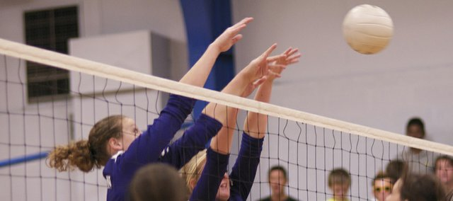 Baldwin's Alexia Stein, left, and Jordan Hoffman team to block an Anderson County attempted kill during the Bulldogs' final match Saturday at the Wellsville tournament. The team won the match, finishing 2-2 on the day.