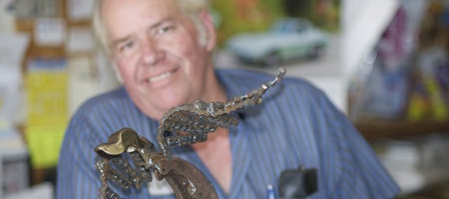 Ken ROBBS creates metal sculptures, such as this duck, from used auto parts found in his garage. Like most of his creations, the duck will be given away. It is to be donated for a Ducks Unlimited gathering Saturday at The Lodge.