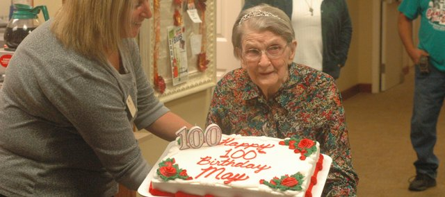 Jennice Baragary, activities director at Vintage Park, presents May Stiglmire with a birthday cake for her 100th birthday Thursday.