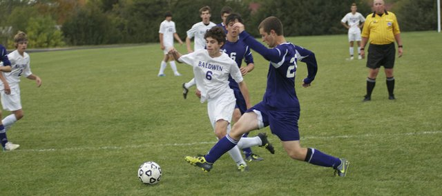 Joel Dixon, 6, battles for control of the ball during Tuesdays Baldwin High School soccer match against Louisburg. Dixon scored two goals in the Bulldogs 4-1 win against the visiting Wildcats.