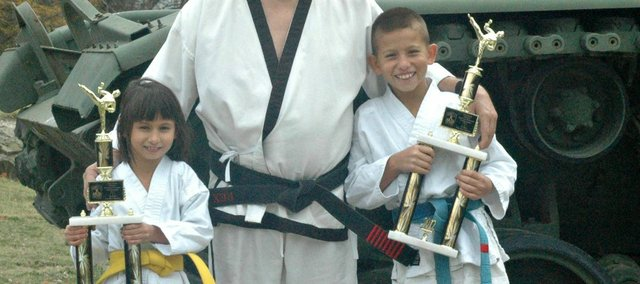 Paige Landrum, left, and Quinton Landrum, right, recently competed at the 39th annual National Tae Kwon Do championships in Kansas City, Kan. They are pictured here with their uncle, Master Rex Hutton of the Tonganoxie Martial Arts Academy.