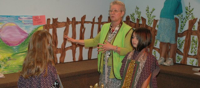 "Rita Robertson (center), workshop director, leads Sunday School second-graders Leah Stutts and Amanda Cline, dressed as priests, in reenacting the Biblical story of Joshua and the city of Jericho Sunday at Elm Grove Baptist Church's new Treehouse Sunday School. Like all of the Treehouse's rooms, Robertson's ""Shining Light Drama"" room is painted to look as though those inside are looking out from the treehouse."