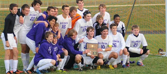 The Baldwin Bulldog soccer team poses with regional championship plaque at the conclusion of Tuesday&#39;s 1-0 victory against Spring Hill.  