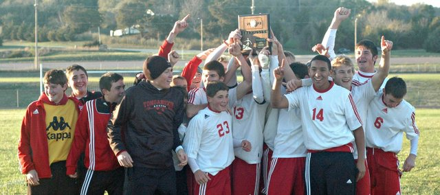 The THS soccer team poses with its regional championship trophy after defeating Basehor-Linwood on Friday.